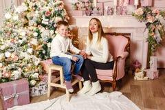 Młoda kobieta i siedmioletni dziecka spojrzenie przy kamerą w Bożenarodzeniowym położeniu Rodzina przy bożymi narodzeniami Mama i zdjęcia royalty free
