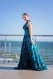 Młoda kobieta i wspaniały zostajemy na szklanym balkonie Powabna dziewczyna w turkusowej sukni na jaskrawym błękitnym dennym tle Zdjęcie Stock