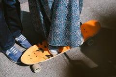 Młoda kobieta jeździć na deskorolce na asfaltowej ulicie w spódnicie Zdjęcie Stock