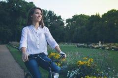 Młoda kobieta jeździecki bicykl w parku Fotografia Stock
