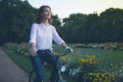 Młoda kobieta jeździecki bicykl w parku Zdjęcie Stock