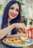 Młoda kobieta je świeżej smakowitej ryba z francuskimi dłoniakami Zdjęcie Stock