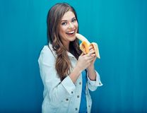Młoda kobieta je banana czuć szczęśliwego po to, aby Fotografia Royalty Free