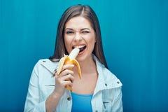 Młoda kobieta je banana czuć szczęśliwego po to, aby Fotografia Stock