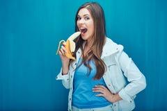 Młoda kobieta je banana czuć szczęśliwego po to, aby Zdjęcie Stock