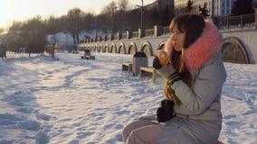 Młoda kobieta je hamburger na zimy ulicie zdjęcie wideo