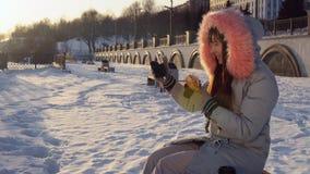 Młoda kobieta je hamburger na zimy ulicie zbiory wideo
