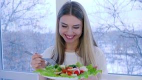 Młoda kobieta je jarskiego posiłek w tle okno w izbowym zakończeniu zbiory wideo
