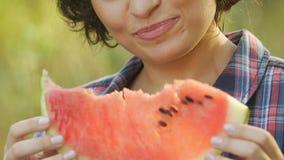 Młoda kobieta je soczystego arbuza na lato pinkinie i ono uśmiecha się, witaminy zbiory