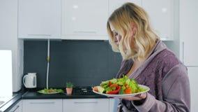Młoda kobieta je zdrowego jedzenie przy kuchnią w kontuszu i napój wodzie od szkła zbiory