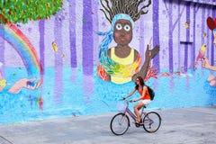 Młoda kobieta jechać na rowerze wzdłuż kolorowej ściany w Montevideo, Urugwaj obrazy stock