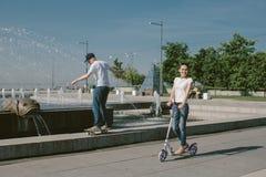 Młoda Kobieta Jedzie hulajnoga z jej mężem na deskorolka A Obraz Royalty Free