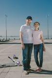 Młoda Kobieta Jedzie hulajnoga z jej mężem na deskorolka A Fotografia Royalty Free