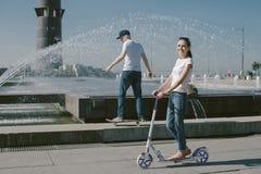 Młoda Kobieta Jedzie hulajnoga z jej mężem na deskorolka A Zdjęcie Royalty Free