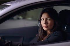 Młoda kobieta jedzie jej samochód przy nocą Zdjęcia Royalty Free