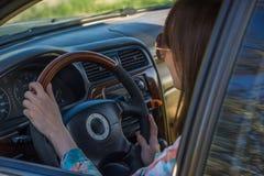 Młoda kobieta jedzie samochód w okulary przeciwsłoneczni Obrazy Royalty Free