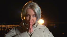 Młoda kobieta jest ono modli się plenerowy przy nocy miastem zdjęcie wideo