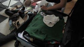 Młoda kobieta jest podsadzkowym walizką z odziewa w mieszkanie pokoju zdjęcie wideo