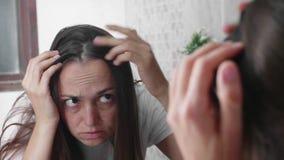 Młoda kobieta jest przyglądająca jej włosy przed lustrem w łazience zdjęcie wideo