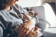 Młoda kobieta jest trzymająca jego ślicznego ciekawego Devon Rex kota i ściskająca Zdjęcie Royalty Free