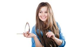 Młoda kobieta jest ubranym błękitną trykotową pulower pozycję na białym tle z odosobnienie punktami z ciemnym włosy Utrzymuje szk Obrazy Stock