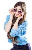 Młoda kobieta jest ubranym błękitną trykotową pulower pozycję na białym tle z odosobnienie punktami z ciemnym włosy Utrzymuje szk Zdjęcie Stock
