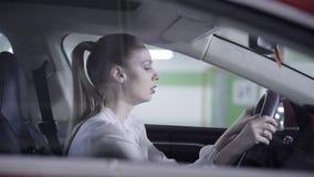 Młoda kobieta jest ubranym białą koszula siedzi w samochodzie, trzyma kierownicę obok garażu zbiory