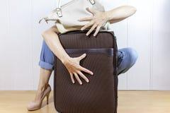 Młoda kobieta jest ubranym cajgi i szpilek cuddles, uściśnięcie bagażu torby obrazy royalty free