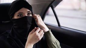 Młoda kobieta jest ubranym czarnego niqab Folowing reguły kobieta jest ubranym niqab podczas gdy jej droga w samochodzie, siedzi  zdjęcie wideo
