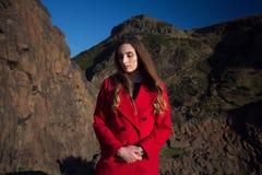 Młoda kobieta jest ubranym czerwonego żakiet patrzeje w dół i nieszczęśliwego obrazy stock