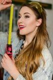 Młoda kobieta jest ubranym drelichowego kombinezon i szkła z długie włosy mieniem w ręk ono uśmiecha się i miarze Fotografia Stock