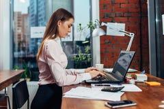 Młoda kobieta jest ubranym formalnego odzieżowego działanie na laptopów pisać na maszynie emailach siedzi przy jej miejscem pracy Zdjęcia Stock