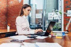 Młoda kobieta jest ubranym formalnego odzieżowego działanie na laptopów pisać na maszynie emailach siedzi przy jej miejscem pracy Zdjęcie Stock