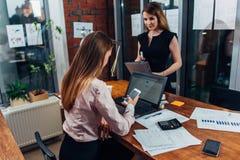 Młoda kobieta jest ubranym formalnego odzieżowego działanie na laptopów pisać na maszynie emailach siedzi przy jej miejscem pracy Obraz Stock
