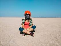 Młoda kobieta jest ubranym hełm dla powozika siedzi w pustyni obraz royalty free