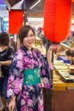 Młoda kobieta jest ubranym japońskiego tradycyjnego kimono z czerwonym lampionem i cieszy się przespacerowanie obrazy royalty free