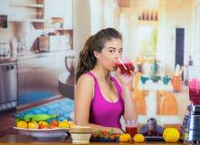 Młoda kobieta jest ubranym menchia wierzchołek cieszy się zdrowego śniadanie, je owoc, pije smoothie i ono uśmiecha się, domowa k Obrazy Royalty Free