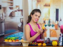Młoda kobieta jest ubranym menchia wierzchołek cieszy się zdrowego śniadanie, je owoc, pije smoothie i ono uśmiecha się, domowa k Zdjęcie Stock