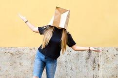 Młoda kobieta jest ubranym papierową torbę nad jej głową przed kolorem żółtym fotografia royalty free