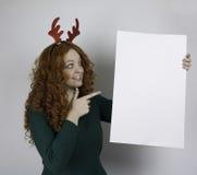 Młoda kobieta jest ubranym poroże i trzyma pustego znaka Zdjęcia Stock