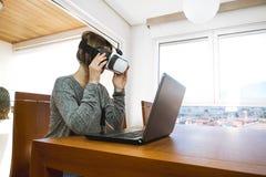 Młoda kobieta jest ubranym rzeczywistość wirtualna szkła i laptop w biurze VR szkła, rozrywka, technologia obrazy stock