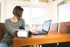 Młoda kobieta jest ubranym rzeczywistość wirtualna szkła i laptop w biurze VR szkła, rozrywka, technologia fotografia royalty free