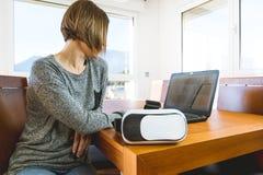 Młoda kobieta jest ubranym rzeczywistość wirtualna szkła i laptop w biurze VR szkła, rozrywka, technologia zdjęcie royalty free