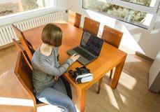 Młoda kobieta jest ubranym rzeczywistość wirtualna szkła i laptop w biurze VR szkła, rozrywka, technologia zdjęcie stock