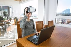 Młoda kobieta jest ubranym rzeczywistość wirtualna szkła i laptop w biurze VR szkła, rozrywka, technologia fotografia stock