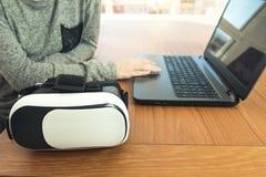 Młoda kobieta jest ubranym rzeczywistość wirtualna szkła i laptop w biurze VR szkła, rozrywka, technologia zdjęcia stock