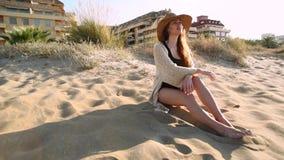 Młoda kobieta jest ubranym słomianego kapelusz relaksuje na plaży zbiory