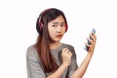 Młoda kobieta jest ubranym słuchawki cieszy się nowego audia tropi bawić się wewnątrz zdjęcia royalty free