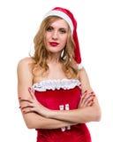 Młoda kobieta jest ubranym Santa Claus odziewa pozować przeciw odosobnionemu bielowi Zdjęcia Royalty Free