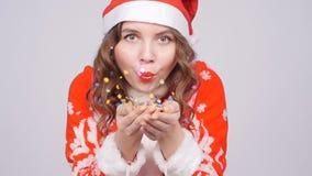 Młoda kobieta jest ubranym Santa ` s kapeluszowych podmuchowych oddalonych confetti zbiory wideo